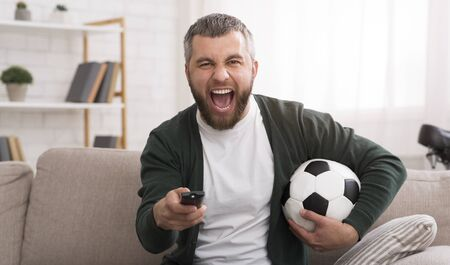 Emotional Middle Aged Bearded Man Watching Football Game On TV At Home, panorama with copy space