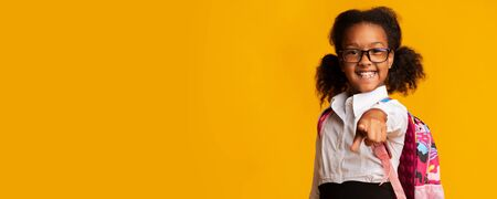 Hey, you. Happy Black Elementary School Girl Pointing Finger At Camera On Yellow Studio Background. Panorama With Copy Space