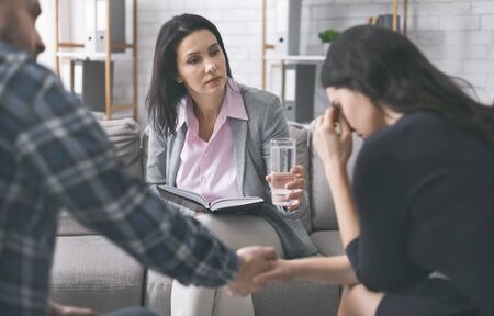 Worried psychologist offering glass of water for crying woman to calm down, man comforting her at psychological consultation