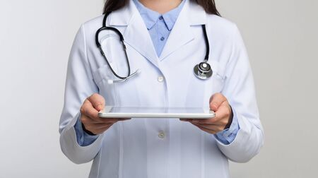 Medical Technologies. Unrecognizable Doctor Holding Digital Tablet Standing On White Background In Studio. Panorama, Cropped