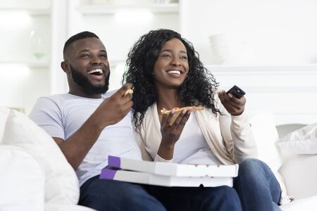 Lovely african american couple sharing pizza and watching comedy show on tv at home