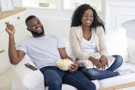 Cheerful black couple watching comedy movie on tv and laughing, enjoying weekend at home.