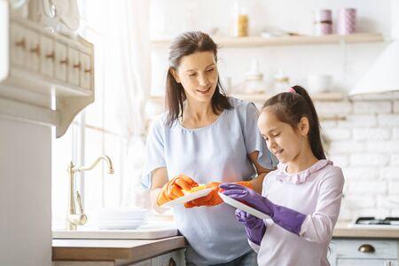 Mano amica. Adolescente sveglio che aiuta sua madre a lavare i piatti in cucina di famiglia