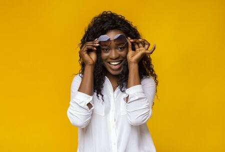 Young Black Woman Playing With Her Sunglasses, yellow studio background