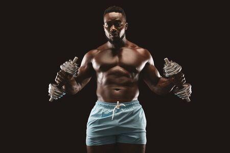 Afrikanischer Sportler, der Hammerlocken mit beiden Händen über schwarzem Studiohintergrund macht