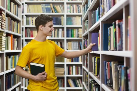 Young caucasian student taking book from bookshelf, studying at library, copy space