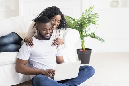 Wife embracing and cheering her husband who working as freelancer at home, copy space Stock Photo