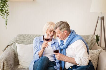 Celebrate anniversary. Happy senior couple drinking wine and talking, sitting on sofa at home