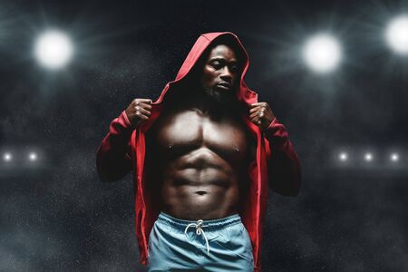 Boxer man workout in boxing ring. African fighter in hoodie, stadium lights background Imagens