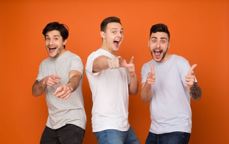 Hey you! Joyful friends pointing fingers at camera over orange background