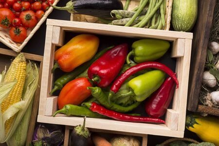 Eco vegetables concept. Different red green farm peppers in wooden box on background Stock fotó