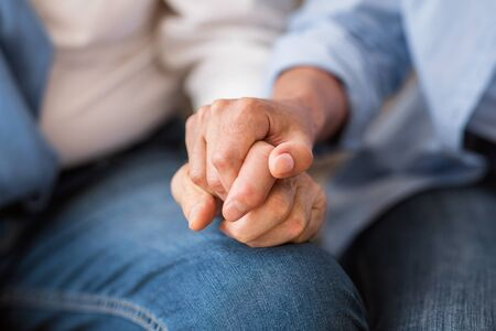 Love and support concept. Senior couple tenderly holding hands, closeup