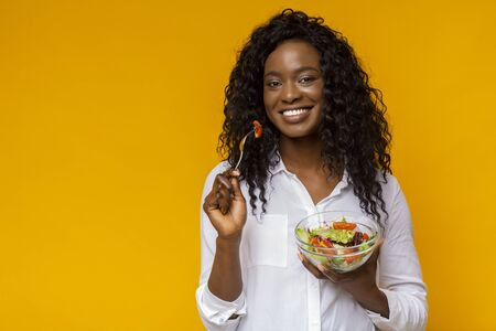 Happy African American Lady Eating Healthy Salad, yellow studio background, copy space