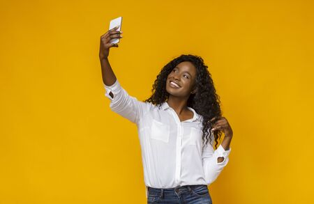Young african woman holding cellphone and making selfie, touching her hair, copy space Фото со стока - 130045967