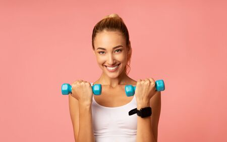 Workout Concept. Positive Millennial Girl Exercising With Dumbbells Over Pink Background. Studio Shot