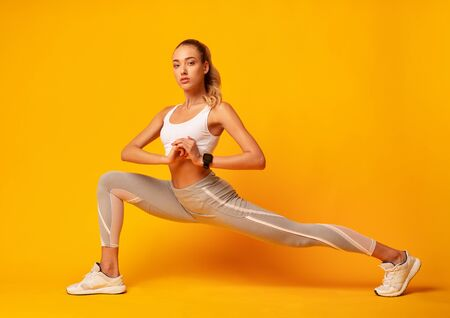 Sporty Girl Doing Deep Lunge Exercise Stretching Legs Over Yellow Background. Studio Shot Фото со стока
