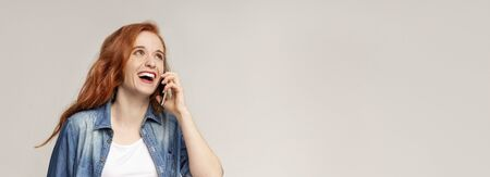 Good news. Positive ginger girl talking on mobile phone, having pleasant call, panorama with copy space