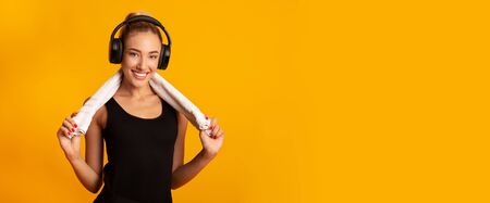 Fitness Music. Positive Girl In Wireless Headphones Holding Towel Standing On Yellow Background In Studio. Panorama, Empty Space Фото со стока