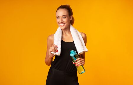 Workout And Hydration. Young Woman Holding Water Bottle And Towel Standing After Exercising On Yellow Studio Background. Фото со стока