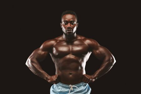 Confident african man demonstrating his muscular chest over black background