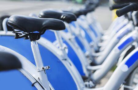 Fietsen te huur in de stad, station met nieuwe soortgelijke fietsen buiten, close-up