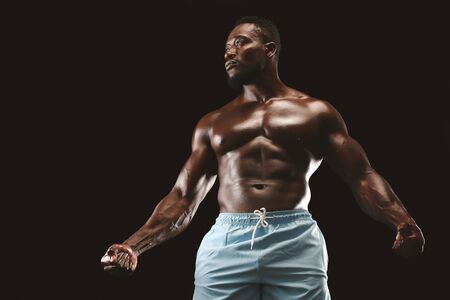 Muscular black sportsman demonstrating musculs over black background, clenching fists, copy space