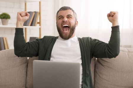 Got Good News. Excited Middle Aged Man Sitting On Couch And Shouting, using laptop Stockfoto - 130285979