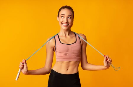Cheerful Slim Girl Holding Jump Rope Over Yellow Studio Background. Fitness Workout Concept