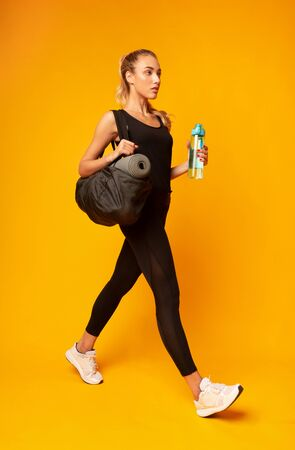 Sporty Lifestyle. Millennial Girl Going To Gym Holding Bag And Bottle Of Water On Yellow Background In Studio. Full Length
