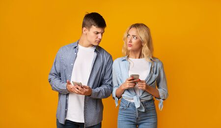 Jealous guy looking at girlfriends cellphone, reading her messages, yellow studio background with copy space