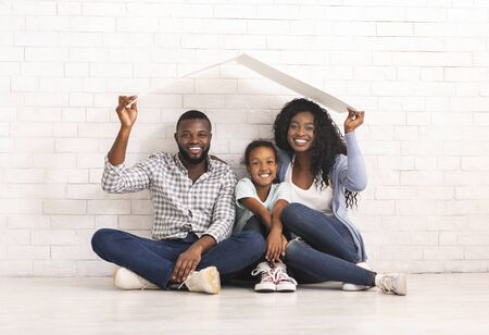 Family Housing Concept. Young Parents And Daughter Sitting Under Roof Dreaming Of New Home. White Brick Wall Background, Copy Space
