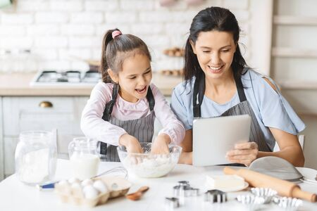 Mother and daughter using digital tablet in kitchen, looking video recipe of dough on internet, copy space