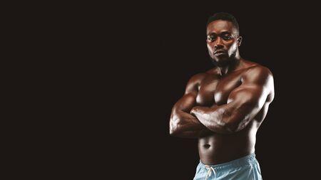 Athlète afro-américain musclé avec les bras croisés regardant la caméra, fond de studio noir, panorama avec espace libre