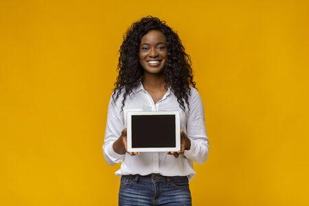 Lächelnde schwarze Frau zeigt leeren digitalen Tablet-Bildschirm, Textfreiraum Standard-Bild