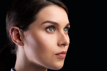 Porträt des weiblichen Gesichtes, das beiseite über schwarzem Studiohintergrund anstarrt. Klonen von Robotern und Menschen. Nahaufnahme