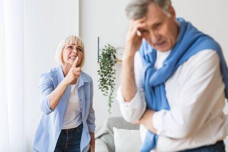 Senior couple having relationship problems, quarrelling at home. Woman shouting at man