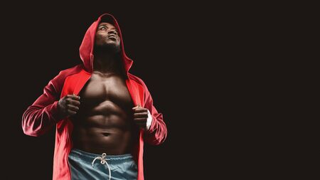 Black muscular fighter in red hoodie, black studio background, panorama with copy space