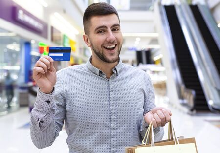 Easy to pay. Happy man with credit card making purchases in shopping mall, copy space Stock fotó