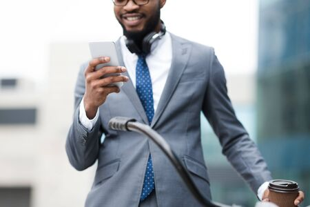 Afro businessman using phone, standing with bicycle near office building, crop Фото со стока