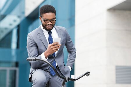 Happy afro businessman texting on smartphone, riding on bicycle to office Фото со стока