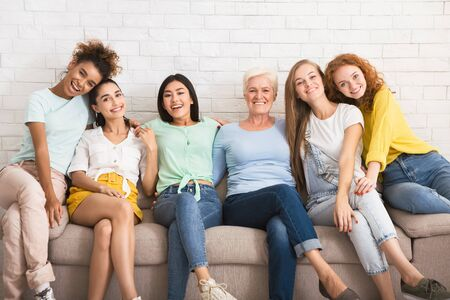 Diverse Women Hugging Smiling At Camera Sitting On Couch Against White Wall Indoor. Equality And Friendship. Banco de Imagens