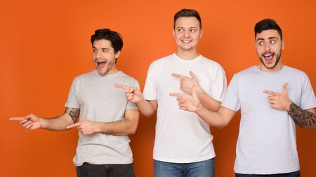 Excited guys pointing fingers away and looking aside over orange studio background