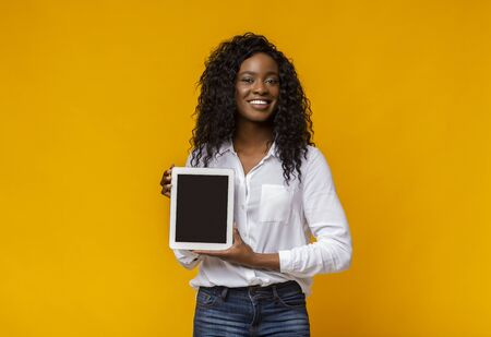 Cheerful African Woman Demonstrating Empty Digital Tablet Screen, free space