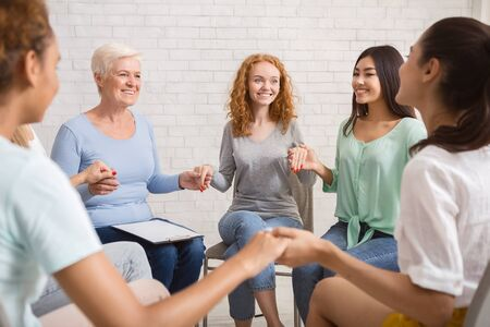 Group Therapy. Smiling Diverse Women Sitting In Circle Holding Hands Indoor. Selective Focus Stockfoto