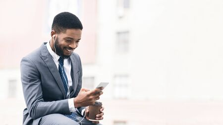 Businessman with coffee using cellphone, having break near office, free space