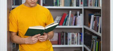 Intelligent cauasian student checking on information in handbook at campus library, free space Stock Photo