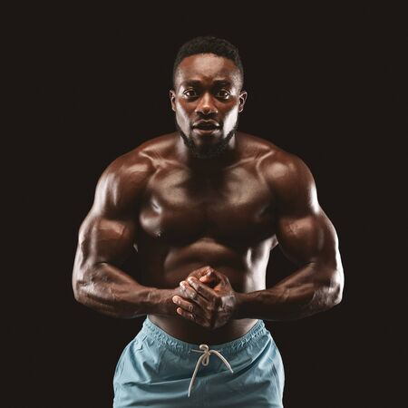 Professional african american sportsman posing on camera, flexing muscles, black studio background