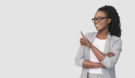Look There. Positive Afro Office Girl Pointing Finger At Empty Space Over White Background. Studio Shot, Empty Space Stok Fotoğraf