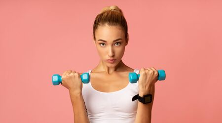 Motivated Fitness Woman Exercising With Dumbbells On Pink Studio Background. Workout Concept. Panorama Stock Photo