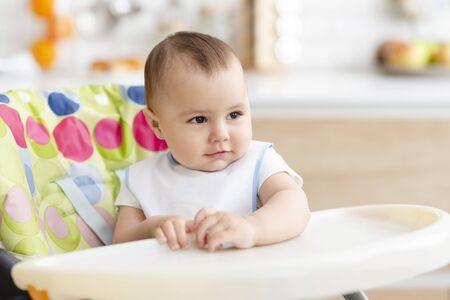 Tempo di pranzo. Adorabile bambino seduto nel seggiolone in cucina, spazio vuoto
